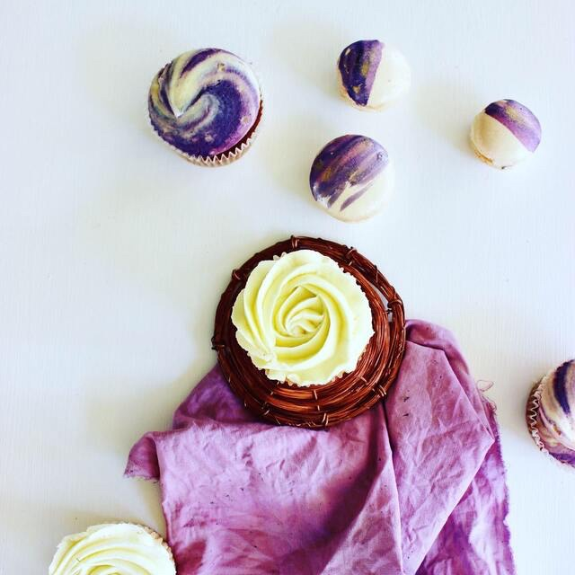 Purple linen tablecloth covered in freshly baked cupcakes and macarons