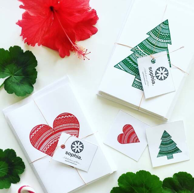 Beautiful and ethical Christmas gift cards styled with red flowers and greenery